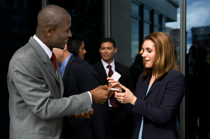 Two business people exchanging business cards. Focus on woman.